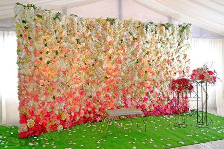 Стену из цветов можно расположить углом или развернуть боковые стенки в форме трапеции