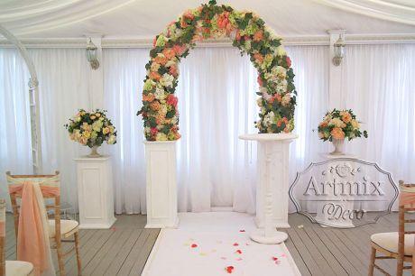 Полукруглая свадебная арка из цветов на белых колоннах