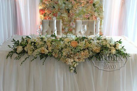 В оформлении свадебного стола стоит горизонтальная, симметричная цветочная композиция